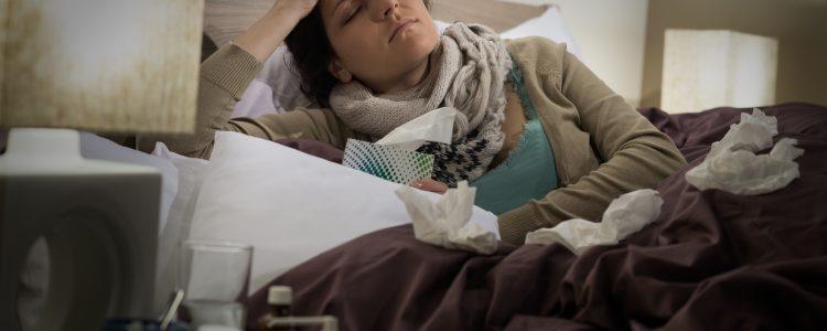Sick woman in bed suffering flu headache