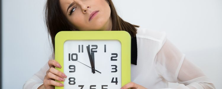 Tired businesswoman sitting at the table with clock. Waiting for break